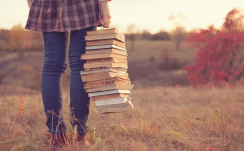 person in a field carrying stack of books wrapped in string